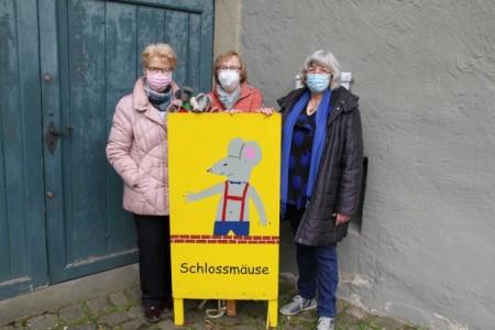 """Haben die Domäne ein letztes Mal hinter sich geschlossen (v.l.): Ulla Rohloff, Elsbeth Heym und Monika Lietz-Heger gemeinsam mit den beiden Maskottchen und dem gelben """"Schlossmäuse""""-Schild, das zu Öffnungszeiten stets vor der Tür stand Foto: Landesverband Lippe"""