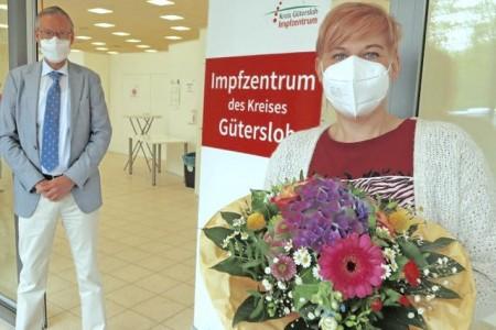 Landrat Sven-Georg Adenauer überreicht Sarah Schuster einen Blumenstrauß. Sie hat die 100.000ste Impfung im Impfzentrum des Kreises Gütersloh erhalten. Foto: Kreis Gütersloh