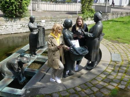 Die Waschfrauen sind eine Station des Audioguides Alexandra Bröckling (li.) und Vivian Fortmann von der Tourist Information Paderborn erfahren beim Waschfrauendenkmal, was die Pader zu berichten hat.Foto:© Verkehrsverein Paderborn e. V.