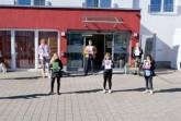Kinder der Grundschule am Schloss (Tobias, Finja, Lotta, Charlotte und Lya) überreichen zusammen mit Lehrerin Alexandra Kehl, Saskia Frei-Klages vom Kreis Lippe und Künstler Ste-fan Schäfer ihre Bilder an Nora Meierhenrich vom Ev. Altenzentrum am Schloss.