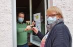Der Leiter des Treffpunkts Johanniskirchhof, Georg Sander, übergibt einen Schlüsselanhänger an eine Bürgerin.Foto © Stadt Minden
