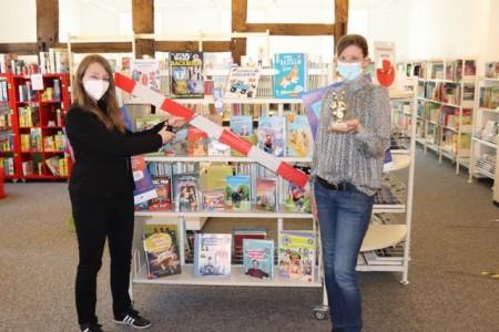 Jennifer Bader (links) und Julia Bröckling vom Team der Stadtbibliothek können es kaum abwarten, das Regal mit neuen Büchern ausschließlich für Sommer-Lese-Club-Mitglieder freizugeben. Foto: Stadt Rietberg