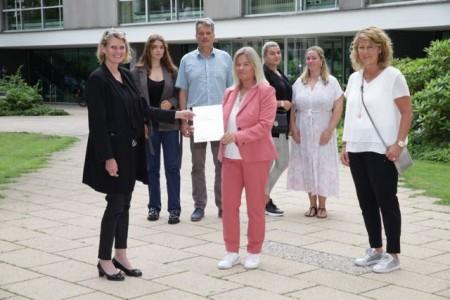 Katja Schultz-Metze (vorne, Mitte) hat im Beisein von Kriminalhauptkommissarin Iris Brinkmann (Kriminalpolizei Gütersloh, vorne, rechts), Ehemann Olaf Metze und ihren drei Kindern Paula (hinten, von links), Lisa und Julia Hufnagel die Ehrenurkunde über die Belobigung des Landes Nordrhein-Westfalen von Regierungspräsidentin Judith Pirscher (vorne, links) entgegengenommen.