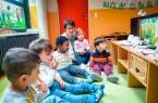 """Monika Neroch-Stern mit den Kindern der Käfergruppe vor einem """"Kamishibai"""" Papiertheater."""