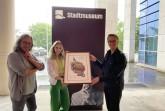 Der Paderborner Künstler Herman Reichold (l.) und seine Assistentin Lara Wenzel übergeben Museumsleiter Markus Runte das erste Exemplar des neuen Libori-Motivs.Foto:© Stadt Paderborn