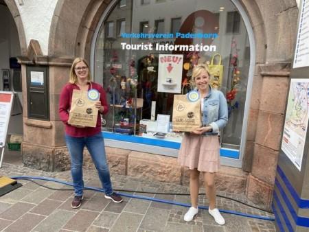 """Anja Vollmer von der Tourist Information Paderborn (l.) und Sinje Mollemeier vom Bürgermeisterreferat, die seitens der Stadt Paderborn die Aktionen der Initiative """"Faires Paderborn"""" unterstützt, freuen sich über die Fairen Tüten.Foto:© Stadt Paderborn"""