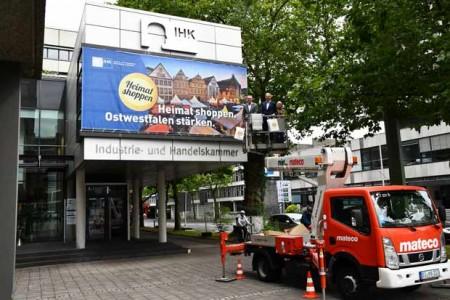 """Der stellvertretende IHK-Hauptgeschäftsführer Harald Grefe (links) und IHK-Präsident Wolf D. Meier-Scheuven präsentieren das Großplakat zur ostwestfalenweiten IHK-Aktion """"Heimat shoppen"""" samt der dazugehörigen Einkaufstaschen, unterstützt von Jan Palmer von der Firma Rosenberger (rechts), der das Plakat anbrachte. Foto: ©IHK"""