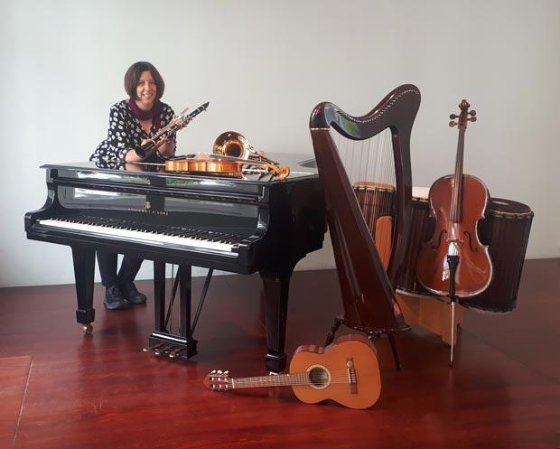 Schulleiterin Susanne Greschok mit einer Auswahl an Instrumenten. Foto: © Johannes-Brahms-Musikschule