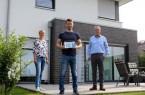 Übergabe der Blauen Hausnummer für ein besonders energieeffizientes Wohngebäude: (v.l.) Andrea Flötotto vom Fachbereich Umweltschutz der Stadt Gütersloh, Hausbesitzer Elvis Dzanko und der städtische Klimaschutzmanager Helmut Hentschel.