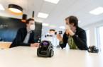 Adrian Freiter (links) und Roman Sliwinski besprechen die nächsten Planungsschritte ihres Projekts, im Vordergrund sieht man einen der Vector-Roboter. (Foto: Felix Hüffelmann / FH Bielefeld)