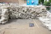 Die Westwand mit dem Entlastungbogen, um den nicht tragfähigen Boden zu überbrücken. Eine dunkle Verfärbung deutet auf eine kreisförmige Grube. Foto: EggensteinExca/R. Gündchen