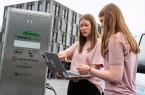Projektmitarbeiterin Katrin Schulte (links) liest die Leistung zum Laden der einzelnen E-Fahrzeuge aus. Das Ziel: Ein möglichst hoher Anteil an regenerativ erzeugtem Strom beim Laden.